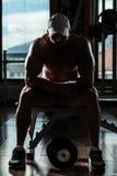休息在健身俱乐部的健康年轻人 免版税库存图片