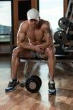 休息在健身俱乐部的健康年轻人 免版税库存照片