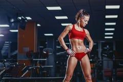 休息在健身房的健身锻炼以后的性感的年轻竞技女孩 免版税库存照片