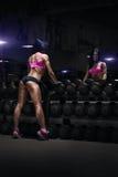 休息在健身房的后面观点的性感的年轻深色的妇女 库存图片