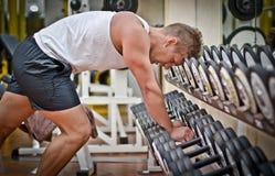 休息在健身房的锻炼以后的英俊的年轻人 免版税图库摄影