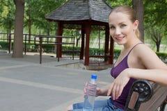 休息在公园的妇女在执行以后。 体育运动健身概念 库存照片