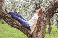 休息在公园的美丽的女孩说谎在树 库存图片