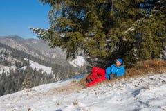 休息在冬天木头的远足者人 库存图片