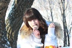 休息在冬天森林里,吃蛋糕和喝茶的女孩 免版税库存照片