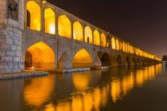 休息在古老桥梁Sio Seh波尔布特附近的人们 库存照片