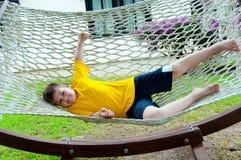 休息在吊床的男孩 库存图片
