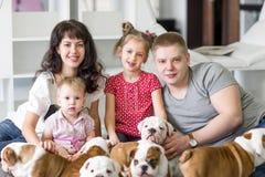 休息在周末与逗人喜爱的小的小狗的美丽的家庭 库存照片