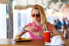 休息在咖啡馆的年轻俏丽的妇女 免版税库存图片