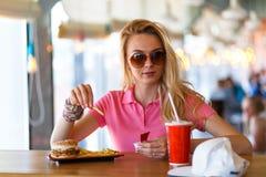 休息在咖啡馆的年轻俏丽的妇女 免版税图库摄影