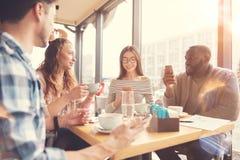 休息在咖啡馆的快乐的国际学生 免版税库存图片