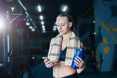 休息在哑铃以后的运动服的性感的健身妇女在健身房行使 有振动器和毛巾的美丽的女孩 免版税库存照片