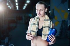 休息在哑铃以后的运动服的性感的健身妇女在健身房行使 有振动器和毛巾的美丽的女孩 免版税库存图片