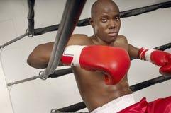 休息在圆环的红色拳击手套的拳击手 免版税库存图片