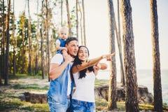 休息在城市之外的一个公园的愉快的年轻三口之家人 女儿在爸爸坐肩膀,并且父母显示direc 免版税库存照片