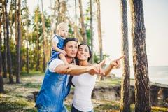 休息在城市之外的一个公园的愉快的年轻三口之家人 女儿在爸爸坐肩膀,并且父母显示direc 库存图片