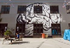 休息在城市的都市部分的青年人有艺术性的画廊和奇怪的长凳的 库存图片