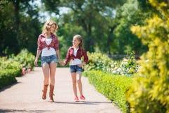 休息在夏天公园的母亲和女儿 库存图片