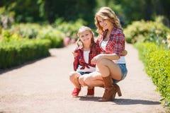 休息在夏天公园的母亲和女儿 免版税库存照片
