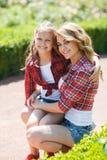 休息在夏天公园的母亲和女儿 图库摄影