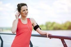 休息在奔跑听的音乐以后的适合的妇女慢跑者 库存图片