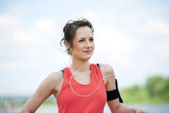 休息在奔跑听的音乐以后的适合的妇女慢跑者 免版税库存照片