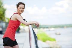 休息在奔跑听的音乐以后的适合的妇女慢跑者 图库摄影