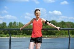 休息在奔跑听的音乐以后的适合的妇女慢跑者 免版税库存图片