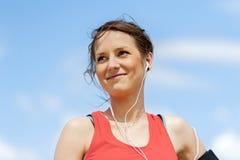 休息在奔跑听的音乐以后的适合的妇女慢跑者 库存照片