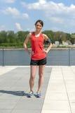 休息在奔跑听的音乐以后的适合的妇女慢跑者 免版税图库摄影