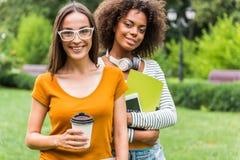 休息在学习以后的愉快的两个女孩户外 免版税库存图片
