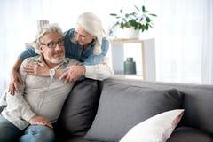 休息在客厅的愉快的资深爱恋的夫妇 库存图片