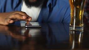 休息在客栈,饮用的桶装啤酒和聊天在电话的非裔美国人的人 影视素材