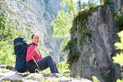 休息在山的女性远足者 免版税库存图片