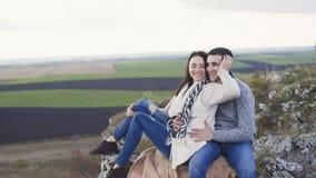 休息在岩石的容忍的可爱的夫妇在大风天 4K 股票视频