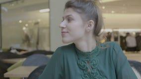 休息在工作饮用的热奶咖啡以后的女性销售主任在微笑和看照相机的购物中心- 股票录像