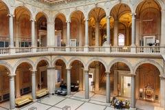 休息在工艺美术博物馆里面庭院的游人与石专栏的 免版税图库摄影