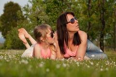 休息在庭院里的母亲和女儿 免版税库存图片