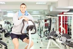 休息在心脏训练以后的年轻微笑的人 免版税库存图片
