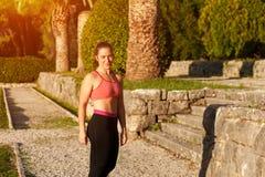 休息在心脏锻炼以后的体育衣服的妇女 免版税库存图片