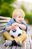 休息在打的小男孩足球/橄榄球赛以后在夏日 图库摄影