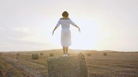 休息在托斯卡纳的一个女孩在意大利,站立在蓝色背景的干草堆上升的和下臂  影视素材