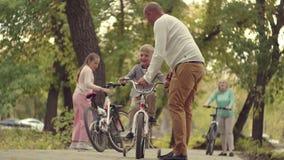 休息在有一个男婴的一个公园的地道愉快的家庭自行车的 在公园生活方式的早期的秋天 家庭 股票录像