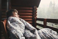 休息在木门廊的毯子的愉快的旅客人有在森林和山的看法 文本的空间 放松的行家  免版税库存照片