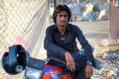 休息在树荫,南部的红外线下的一名阿富汗摩托车骑士的画象 免版税图库摄影
