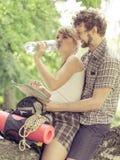 休息在森林饮用水的夫妇远足者 免版税图库摄影