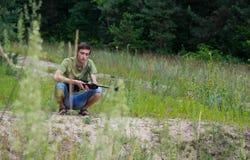 休息在气枪射击以后的年轻人 免版税库存照片
