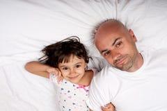休息在河床上的父亲和女儿 免版税库存照片