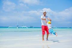 休息在海滩的愉快的家庭在夏天 有基于海滩的儿子的父亲 父亲和他可爱的矮小的儿子 免版税库存照片