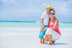 休息在海滩的愉快的家庭在夏天 有基于海滩的男孩的母亲 年轻母亲和她可爱的矮小的儿子 库存照片